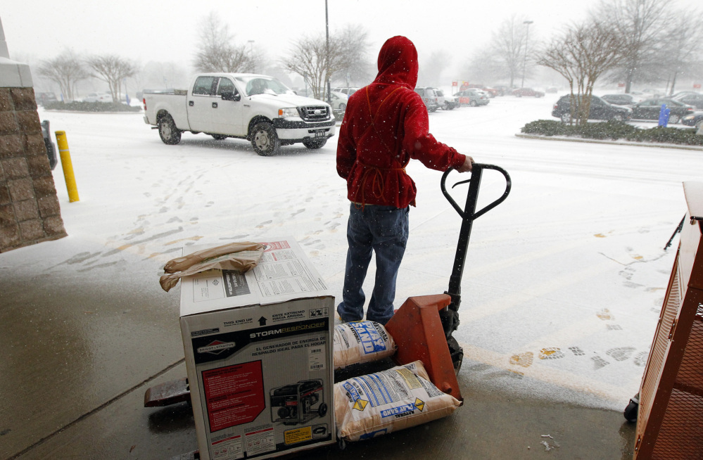Home Depot employee Chris Craft pulls a generator and some sand to the front of the store for a customer in Cary, N.C., earlier this month. Home Depot Inc. estimated it lost $100 million in January because of weather.