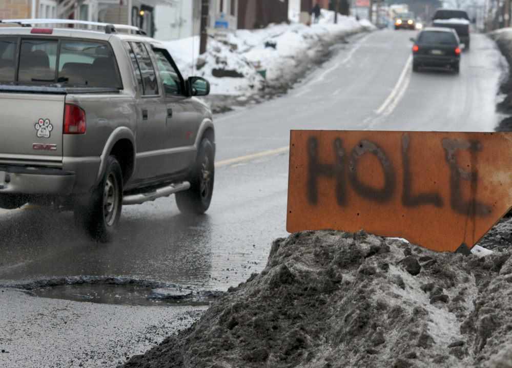"""A sign warns motorists of a pothole in Pottsville, Pa. A report estimates that """"unacceptably rough"""" roads cost the average urban driver $377 a year in repairs."""