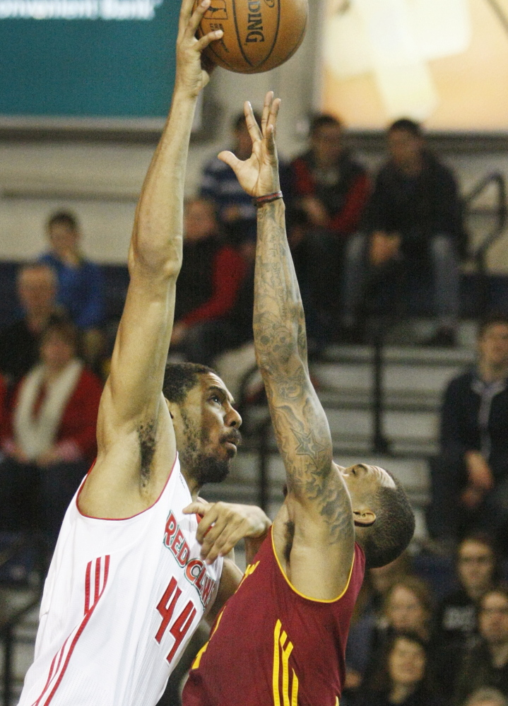 Zeke Marshall, left, of the Red Claws reaches high over Gilbert Brown of the Canton Charge as he takes a shot during Maine's 110-105 win Thursday at the Portland Expo.