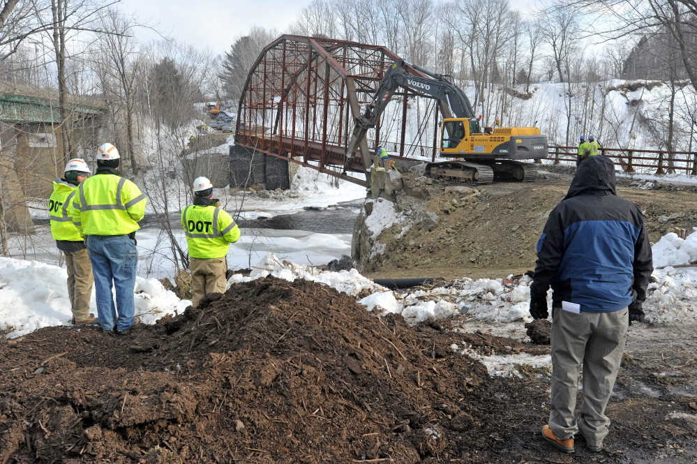 An excavator digs the embankment away from the New Sharon bridge next to Route 2 during demolition Thursday.