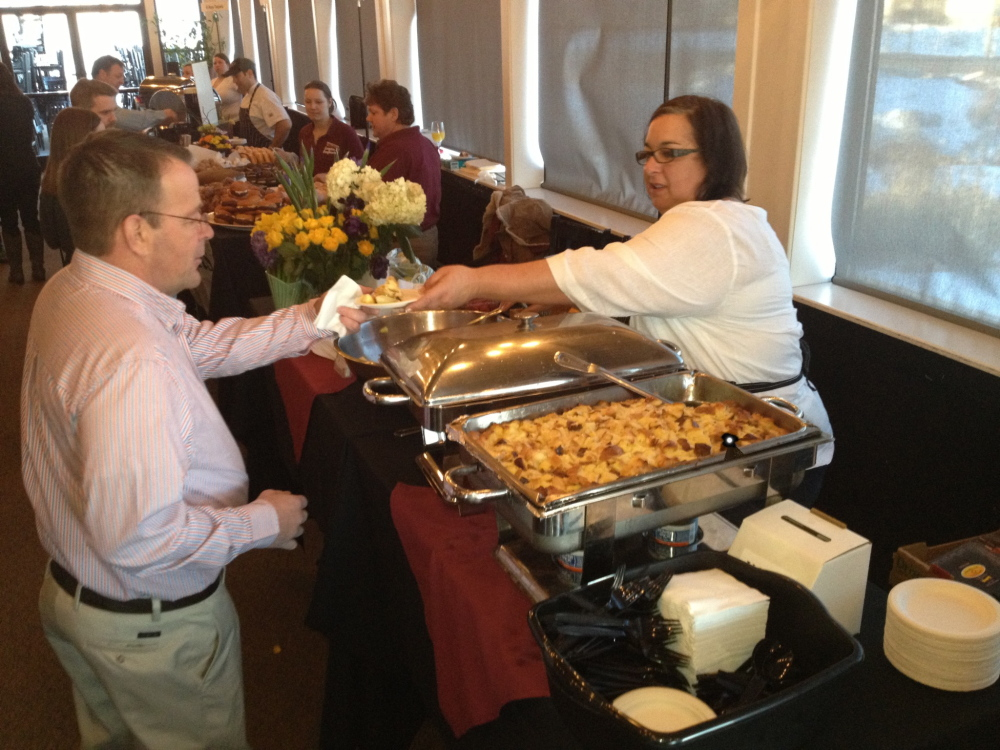 Lisa Kostopoulos serves Creme Brulée French Toast to first arrivals at the Incredible Breakfast Cookoff at Sea Dog Brewing in South Portland.