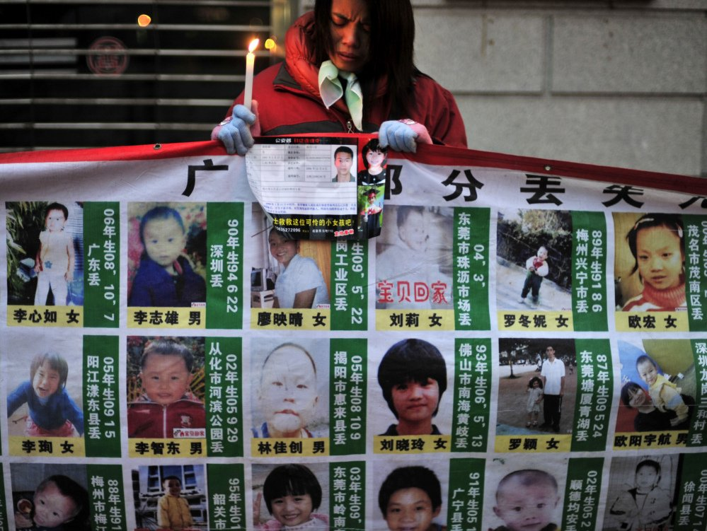 A woman holds a candle behind a board showing photos of missing children during a campaign to search for them in Wuhan, in central China's Hubei province.