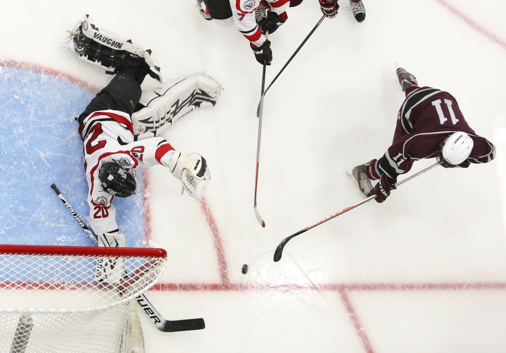 Aidan Black of Greely tries to slip the puck past Zachary Hand of Camden Hills, Friday, Feb. 28, 2014, during the 2nd period of the Class B West semifinal game at the Colisee in Lewiston.