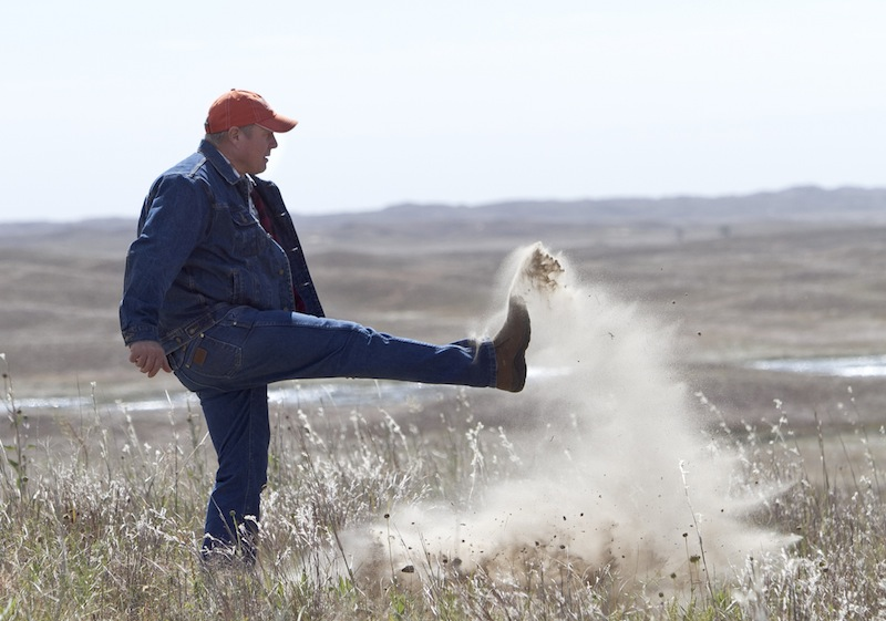 Nebraska rancher Bruce Boettcher, who opposes the Keystone XL pipeline, kicks up sand on his land, to demonstrate the fragility of the sand hills near the planned route of the pipeline.
