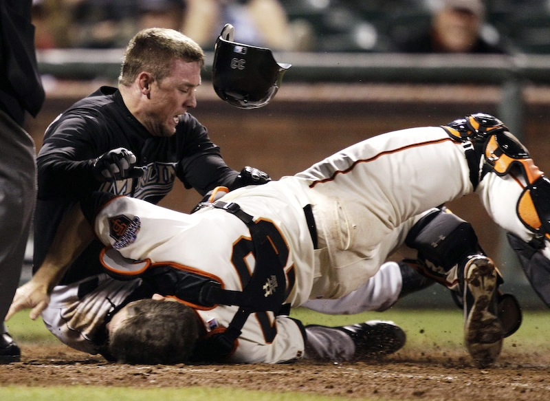 In this May 25, 2011 file photo, Florida Marlins' Scott Cousins, top, collides with San Francisco Giants catcher Buster Posey (28) on a fly ball from Emilio Bonifacio during the 12th inning of a baseball game in San Francisco. Cousins was safe for the go ahead run. A new rule, 7.13, was adopted by MLB and the players' association on a one-year experimental basis, the sides said Monday, Feb. 24, 2014. The umpire crew chief can use the new video-review system to determine whether the rule was violated.