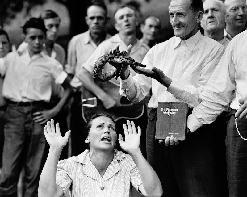 "In this Aug. 22, 1944 file photo, members of the Pentecostal Church of God, a faith healing sect, surround a woman who has ""Got the Spirit"" as a man holds a snake above her head in Evarts, Ky. Although a Kentucky statute passed in 1940 prohibits the handling of snakes in connection with religious services, this sect revived the ritual after the recent death of a native of the region who was bitten by rattlesnake. 1940s 40s Animal Back Woods Bible Book Charmer Christians Cult Danger Eerie Event Fear Guitar Handler Kneeling Men Odd Offbeat Religion Risk Rural Sect Serpent Snake Speaking in Tongues Spirituality Standing State Strange Trance Trust Watching Women"