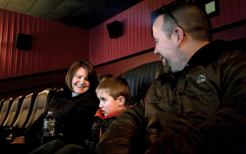 "Erin and Aaron Geyer of Parsonsfield and their son, Ethan, 6, watch a sensory friendly showing of ""The Lego Movie"" for kids with autism at Cinemagic Grand in Clarks Pond in South Portland in February. The government's estimate of autism has moved up again to 1 in 68 U.S. children, a 30 percent increase in two years."