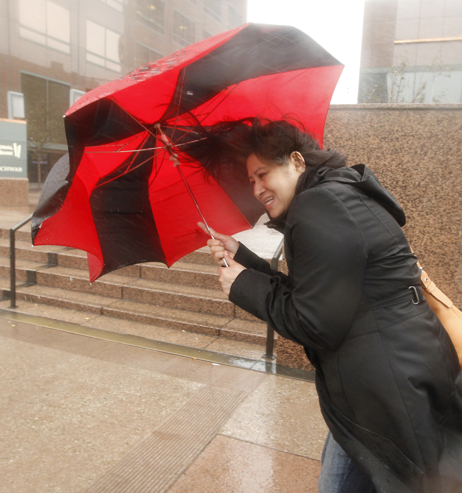 A pedestrian blocks heavy winds with her umbrella in Los Angeles.