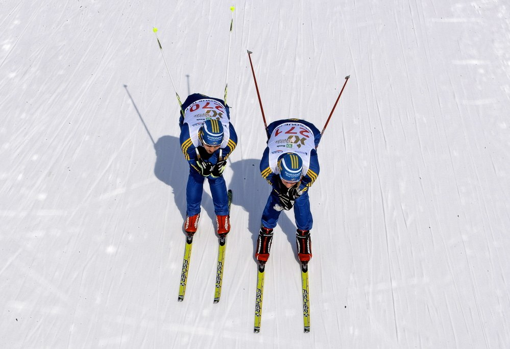 Two Swedish skiers head down a trail at the Nordic Heritage Center in Presque Isle on Friday during a practice run. Athletes from around the world got a cold taste of competing in Maine as the wind chill was at minus-2.