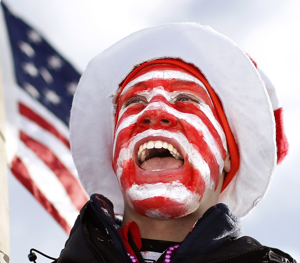 With his face painted and a large American flag in hand, Austin Huneck cheers for members of the U.S. biathlon team.