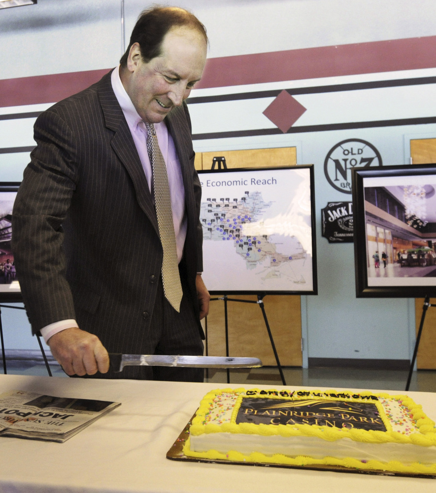 Penn National Gaming President Timothy Wilmott cuts a cake at a party Friday after Massachusetts granted the company a five-year operating license for expanded gambling.