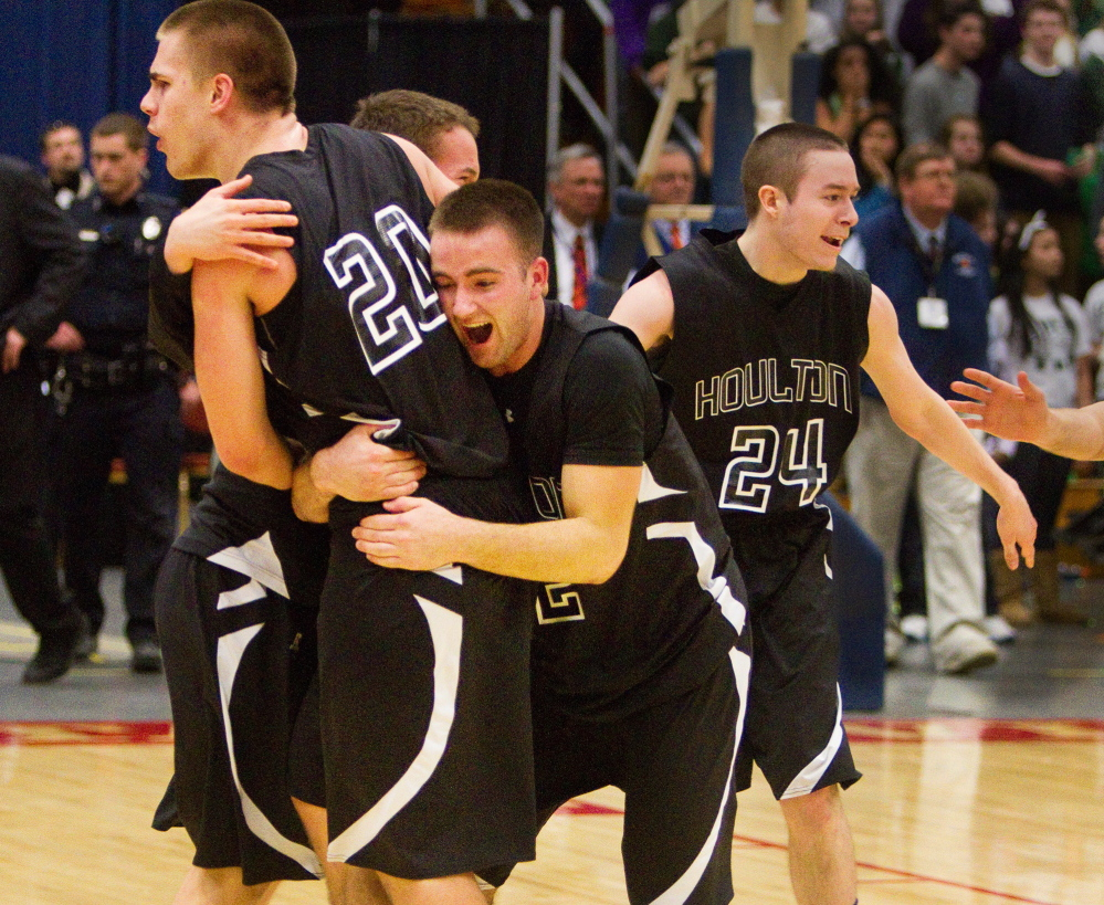 Houlton's Kyle Bouchard is swarmed by teammates after hitting the winning free throws to defeat Waynflete in the Class C boys' basketball state championship game Saturday night at the Augusta Civic Center.