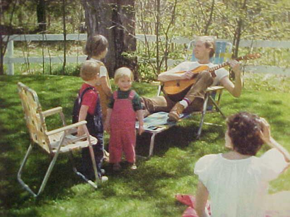 Karmo Sanders, with back to the camera, and her family in Portland in the late 1970s: daughter Hanna (tallest child facing away); daughter Jennywren (in red overalls); a cousin (in blue overalls); and husband, Jerry (with guitar).