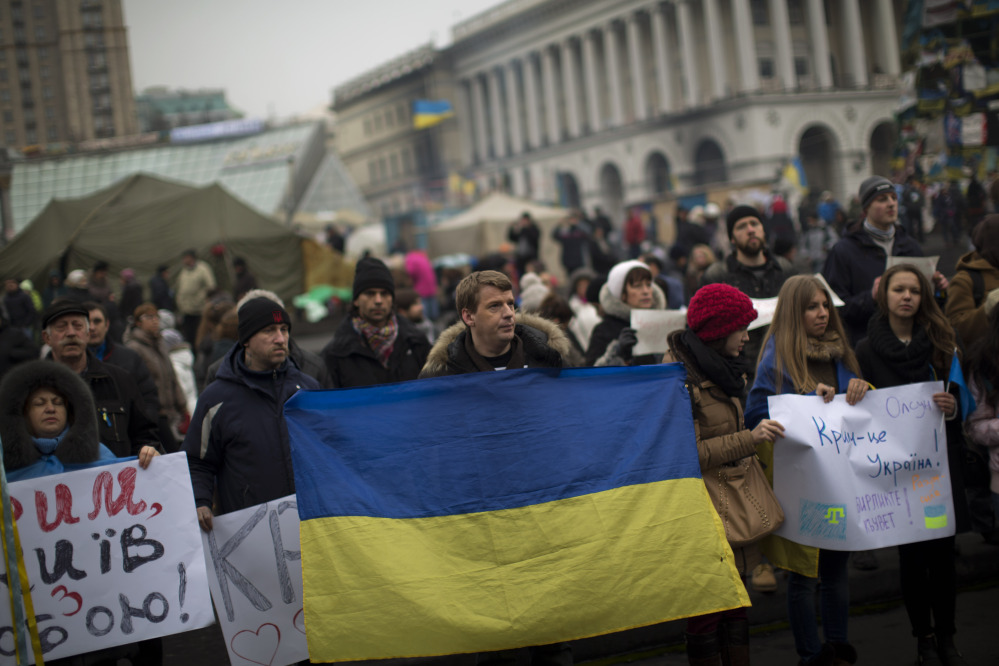 Protesters, one them holding a Ukraine flag, demonstrate against the military intervention of Russia in Crimea as they gather in Kiev's Independence Square, the epicenter of the country's current unrest, on Saturday.