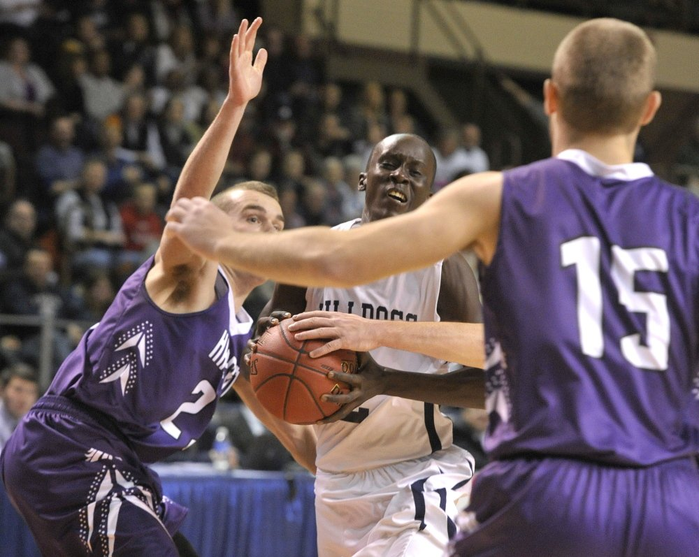 Portland's Steve Alex drives the lane between Hampden's Zach Gilpin and Cameron Scott during the Class A boys' basketball state championship game Saturday at the Cumberland County Civic Center.