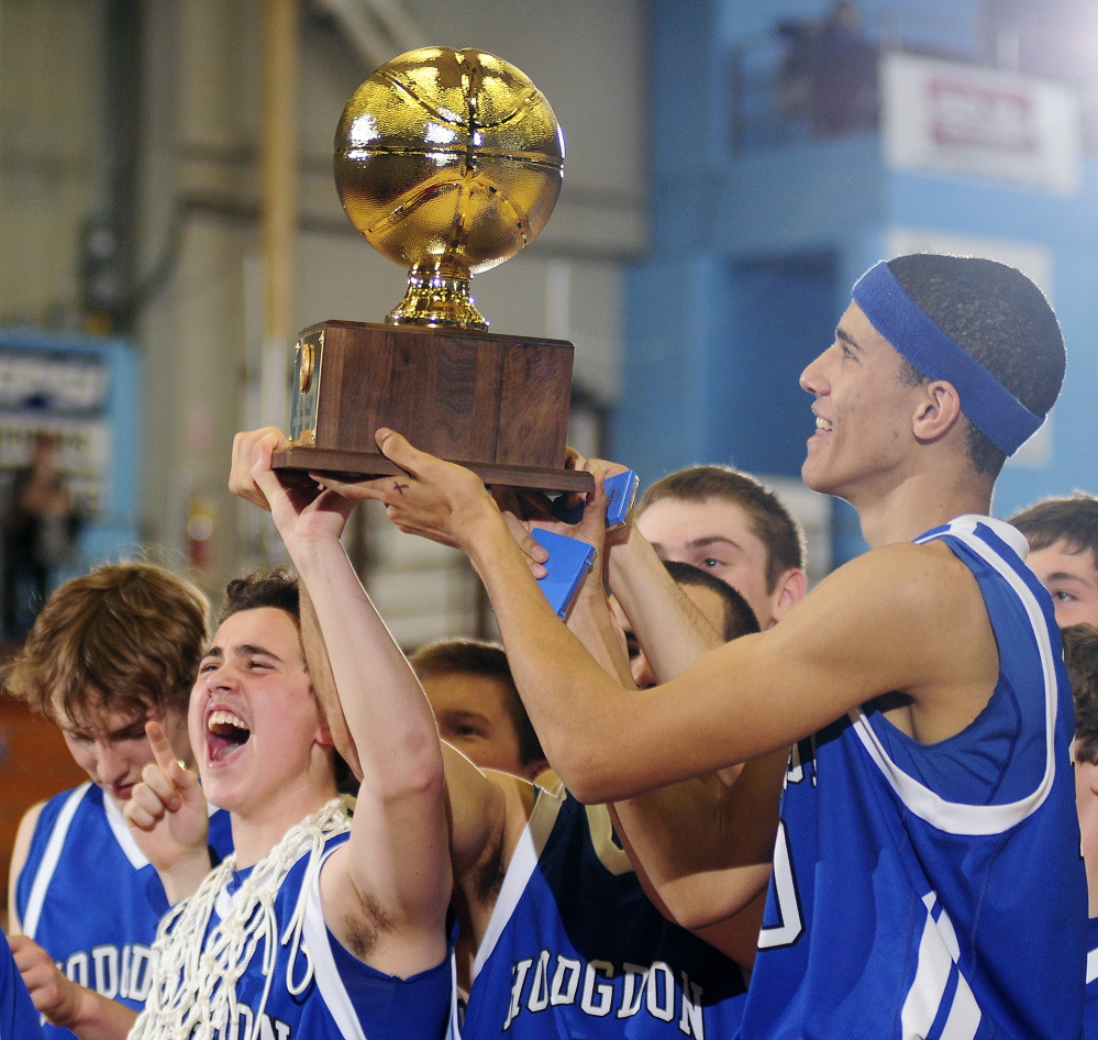 Hodgdon players hold the Gold Ball aloft after they beat Valley 54-49 to win the Class D boys' basketball state championship Saturday at the Augusta Civic Center.