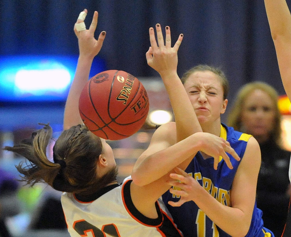 Anna Carrier, left, of Forest Hills gets tangled up with Washburn's Carsyn Koch during the Class D girls' basketball state championship game Saturday afternoon at the Augusta Civic Center. Washburn earned its fourth consecutive state title with a 78-40 win.
