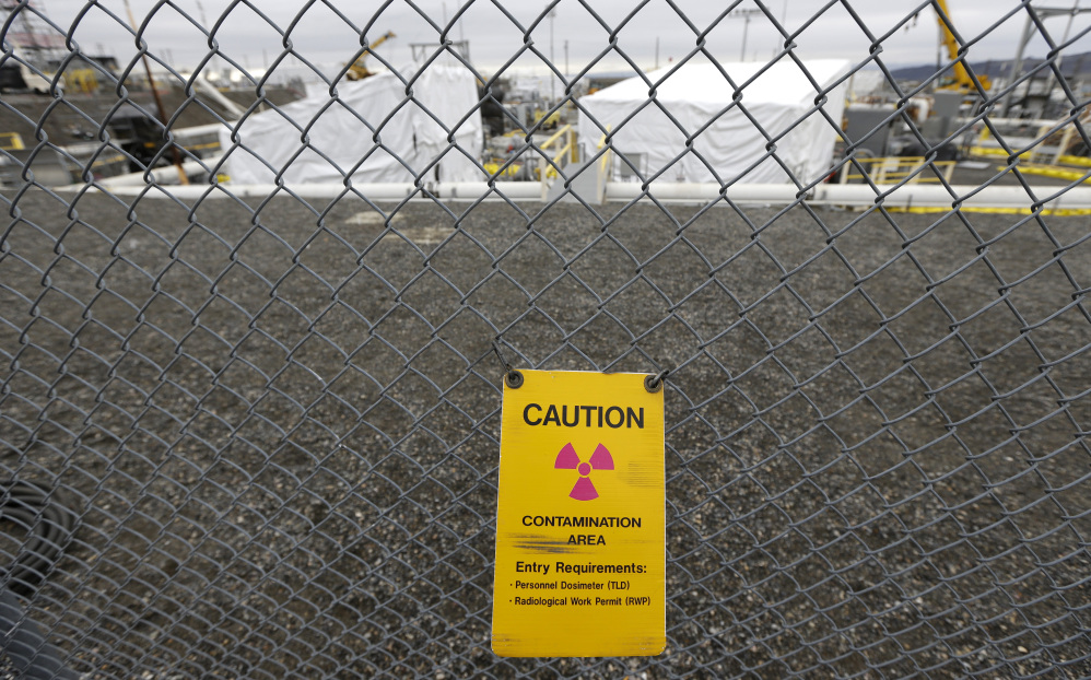 A sign warns of possible radiation at a tank farm at the Hanford Nuclear Reservation near Richland, Wash. Documents obtained by the Associated Press show that there are significant construction flaws in some newer, double-walled storage tanks at the nuclear waste complex.