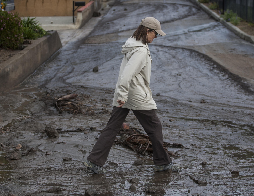 A woman walks over the mud and debris Saturday in Glendora, Calif. A burst of heavy showers before dawn caused another round of mud and debris flows in the city.