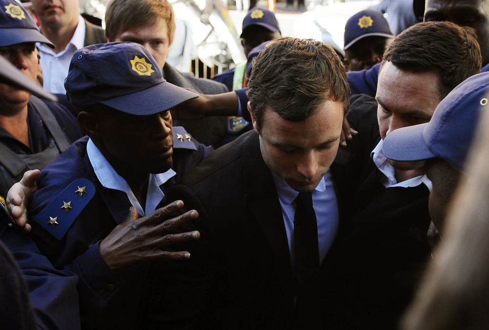Oscar Pistorius, center, arrives outside the magistrates court in Pretoria, South Africa, in August 2013 where he was indicted on charges of murder and illegal possession of ammunition for the shooting death of his girlfriend Reeva Steenkamp. Pistorius goes on trial on Monday.