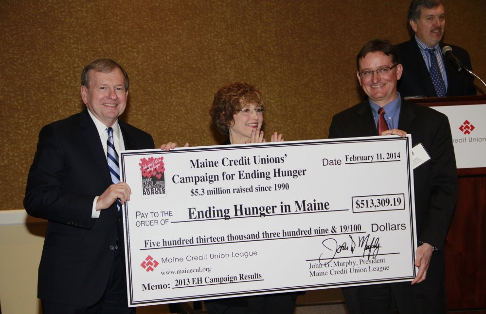 John Murphy, president of the Maine Credit Union League, Sue Mitchell and Luke Labbe, chairman of the league's Social Responsibility Committee, display a check representing the record amount of $513,309.19 raised through the Maine credit unions' Campaign for Ending Hunger in 2013.