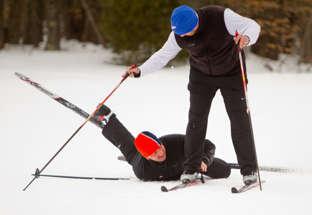 Charles McIntosh of Ohio, on the ground, tags teammate Jeff Steffen of Wisconsin during a biathlon at Pineland Farms in New Gloucester on Sunday.