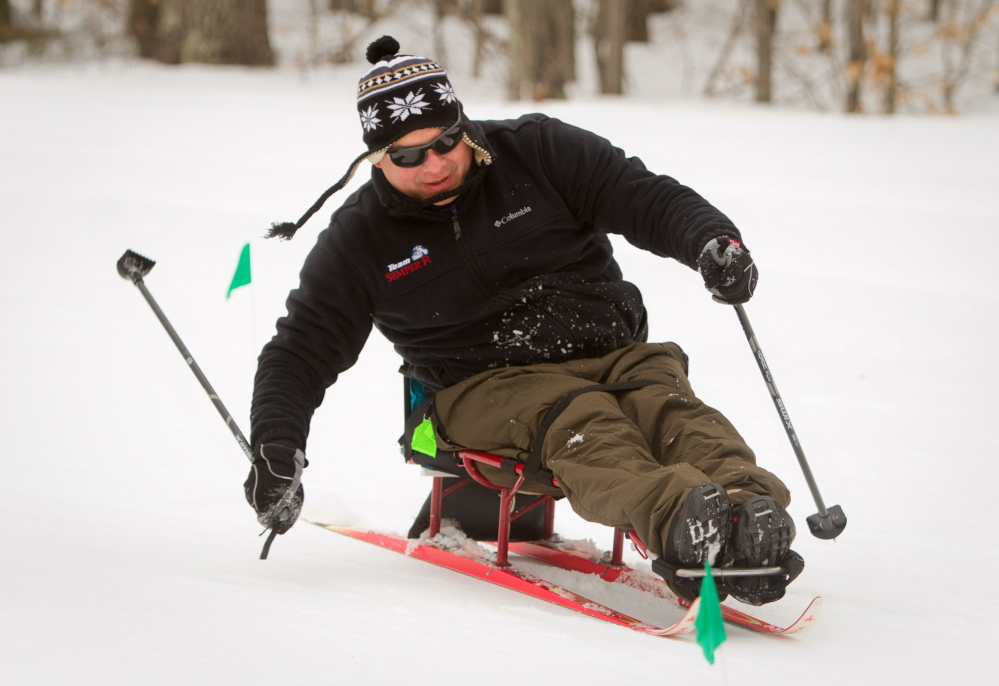 "Ernesto Aquino propels himself on a ski sled during a biathlon at Pineland Farms in New Gloucester on Sunday. ""This is a great place for me,"" Aquino said. ""It helps me relax."""