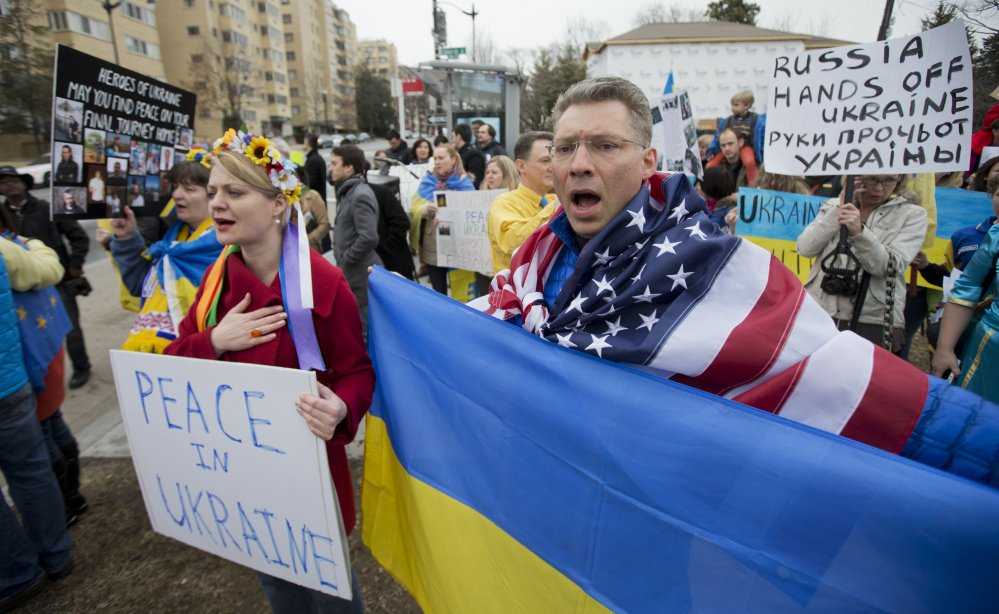 Moscow-born Dmitry Savransky, right, who holds dual citizenship, American and Russian, joins his Ukrainian wife, Natalya Seay, left, during a protest rally in front of the Russian embassy in Washington on Sunday.