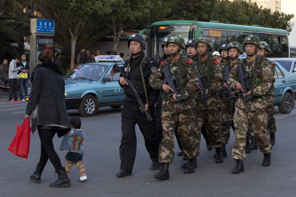 Armed police and paramilitary members patrol a street Monday near the Kunming Railway Station, where knife-wielding attackers slashed scores of people Saturday, leaving 29 dead. Four of the attackers were killed and four suspects have been arrested.