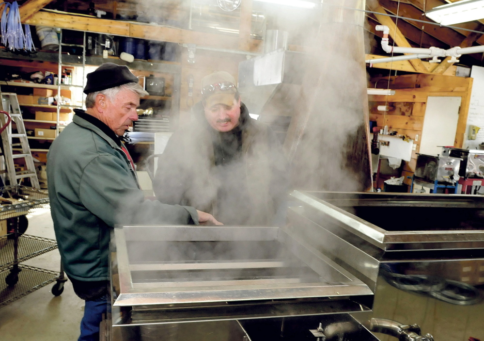 Bob Bacon, left, of the Bacon Farm in Sidney, speaks with Jim Wright of the Apple Ridge maple syrup operation in Cornville as steam rises from a sap evaporator in Sidney on Monday. Bacon said it was the second time he boiled syrup this season and expects his operation to increase this weekend as temperatures rise.