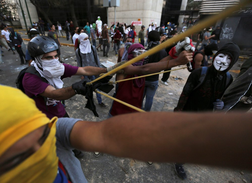 Demonstrators use a giant slingshot to launch stones at Bolivarian National Police during clashes in Caracas, Venezuela, Monday. Venezuelan opposition leader Henrique Capriles called for citizens to begin organizing committees that could sustain the pressure that continuing street protests have placed on the government of President Nicolas Maduro.