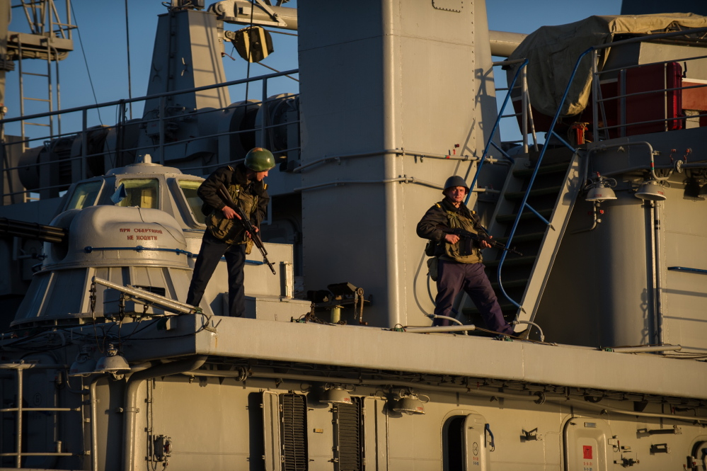 Ukrainian seamen stand guard on the Ukrainian navy ship Slavutich in the harbor of Sevastopol, Ukraine, on Monday. The Ukrainian Defense Ministry said Russian forces that have overtaken Ukraine's strategic region of Crimea are demanding that the ship's crew surrender.