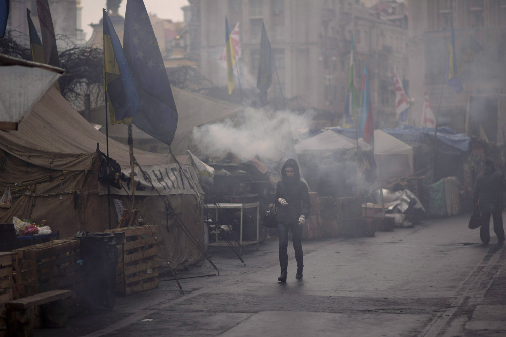 A woman walks past tents erected by protesters who oppose ousted Ukrainian president Viktor Yanukovych, at Kiev's Independence Square, on Monday.