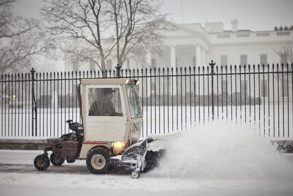 The sidewalk in front of the White House is cleared of snow on Monday. The National Weather Service issued a Winter Storm Warning for the greater Washington Metropolitan region, prompting area schools and the federal government to close.