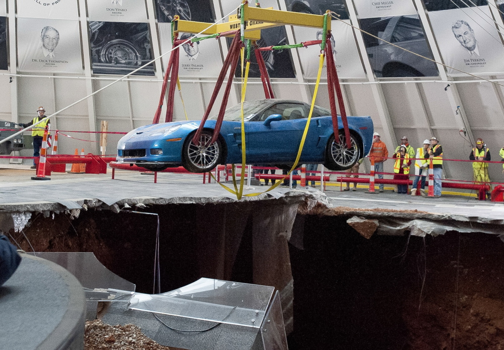 One of eight Chevrolet Corvettes is removed from a sinkhole Monday at the National Corvette Museum in Bowling Green, Ky. On Feb. 12, a sinkhole swallowed eight prized cars, piling them in a heap amid loose dirt and concrete fragments.