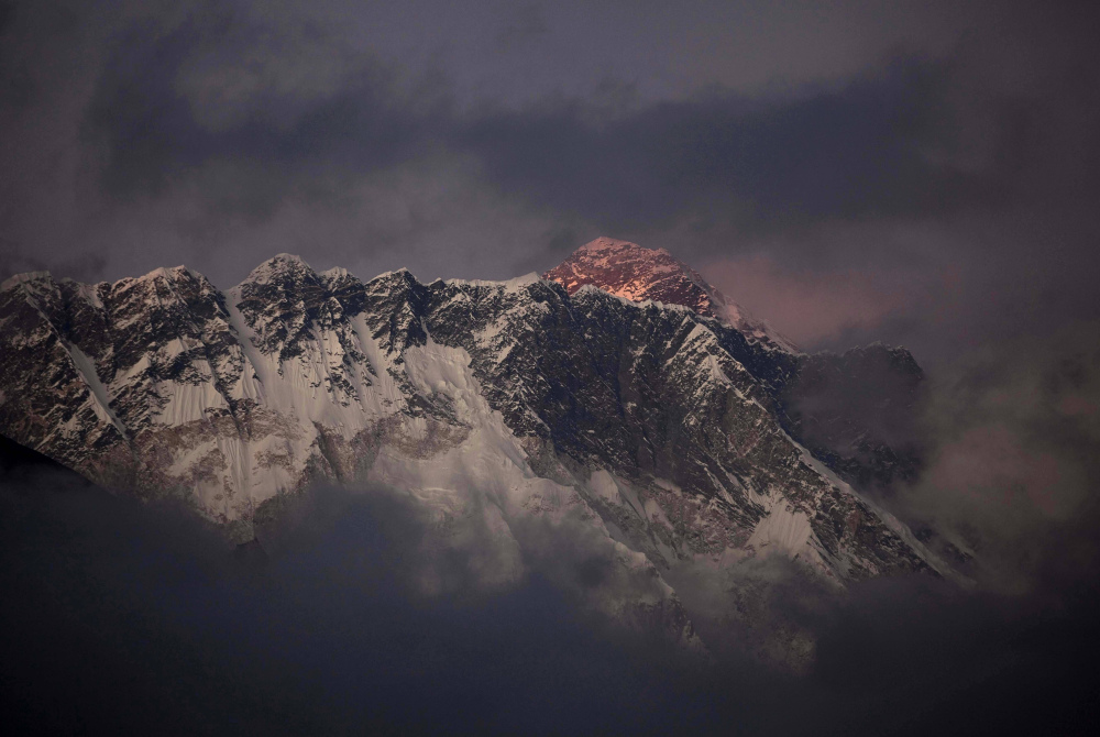 The last light of the day sets on Mount Everest as it rises behind Mount Nuptse in Nepal. The Everest climbing season began Saturday with new rules that require climbers to bring down at least 17.6 pounds of their personal garbage.