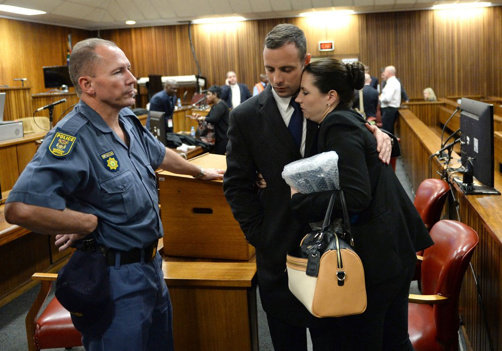 Oscar Pistorius hugs his sister, Aimee, inside court at the end of the second day of his trial at the high court in Pretoria, South Africa, on Tuesday. Pistorius is charged with murder in the shooting death of his girlfriend, Reeva Steenkamp, on Valentines Day in 2013.