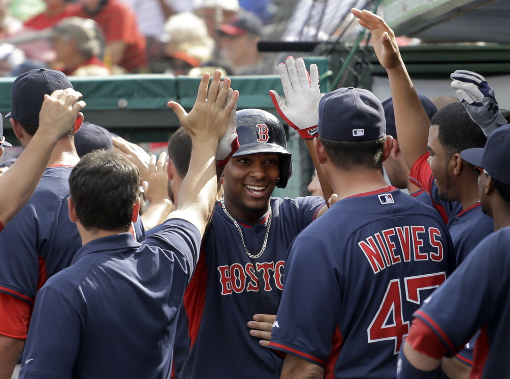 Xander Bogaerts of the Boston Red Sox is welcomed by teammates after hitting a two-run homer Wednesday in the sixth inning of an 8-6 loss to the St. Louis Cardinals in a spring-training game at Jupiter, Fla.