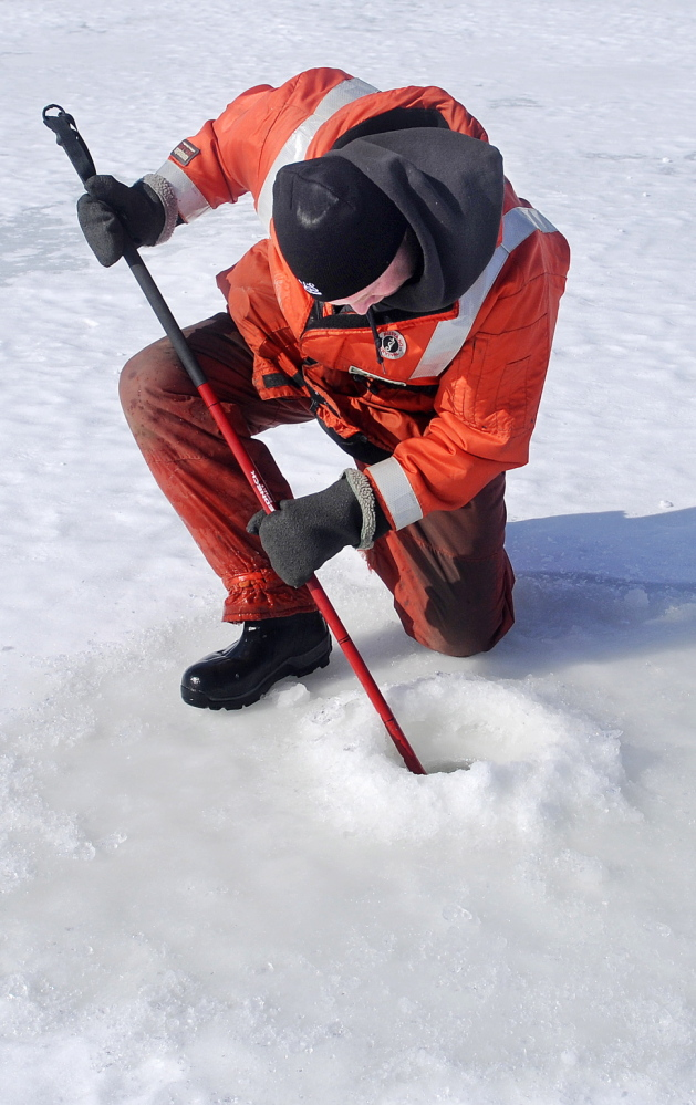 U.S. Geological Survey employee Gregory Stewart inspects the depth of ice on the Kennebec River Tuesday between Dresden and Richmond.