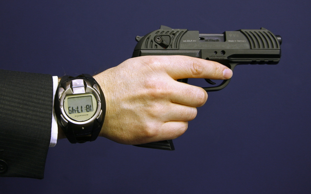 A man holding a prototype of a smart gun by Armatix also wears the gun's security watch.