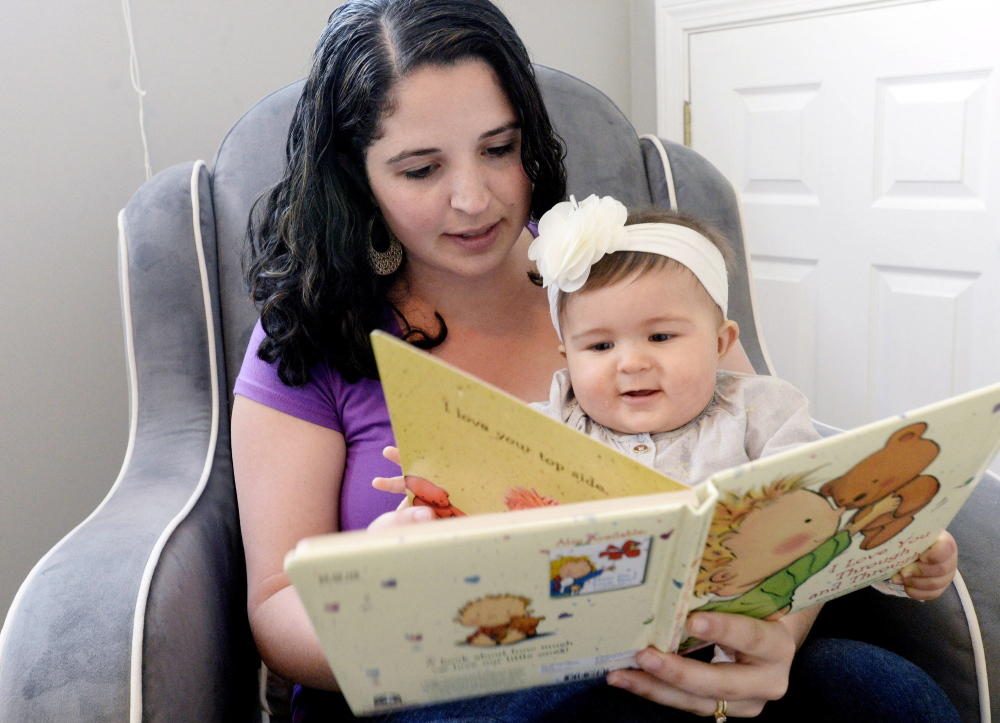 "Hannah Richards of Windham reads to her daughter, Mia, at their home Thursday. ""It's a big help,"" she said of the $500 grant."