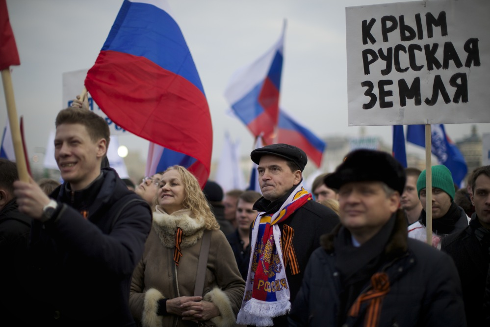 "Pro-Putin demonstrators hold Russian national flags and posters reading ""Crimea is Russia!"" as they gather in Moscow's Red Square on Friday. Leaders of both houses of parliament said they would support a vote by Crimeans to split with Ukraine and join Russia – signaling for the first time that the Kremlin was prepared to annex the strategic region."