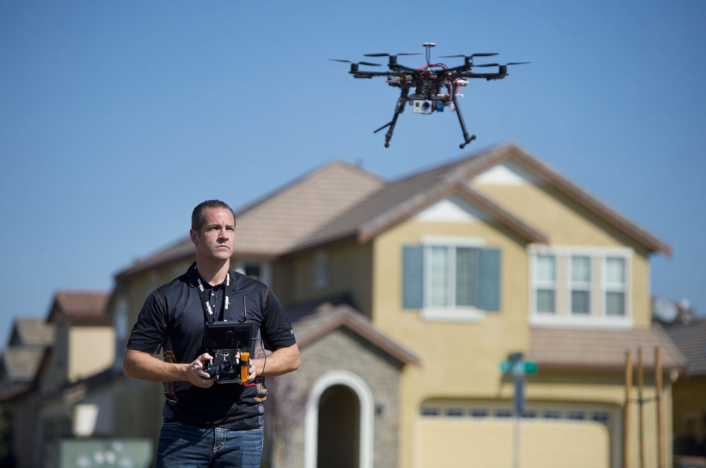 "Christopher Brown of Next New Homes Group uses a multi-rotor drone to take aerial video of a house in Sacramento, Calif. He calls the drones a ""game-changer"" for marketing homes."