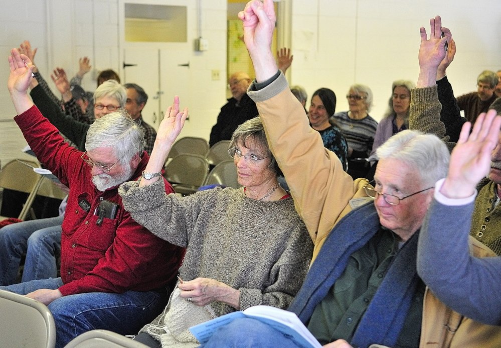 Peter Kallin, left, Sue Greenan and Dick Greenan vote from the front row Saturday during the Rome town meeting.