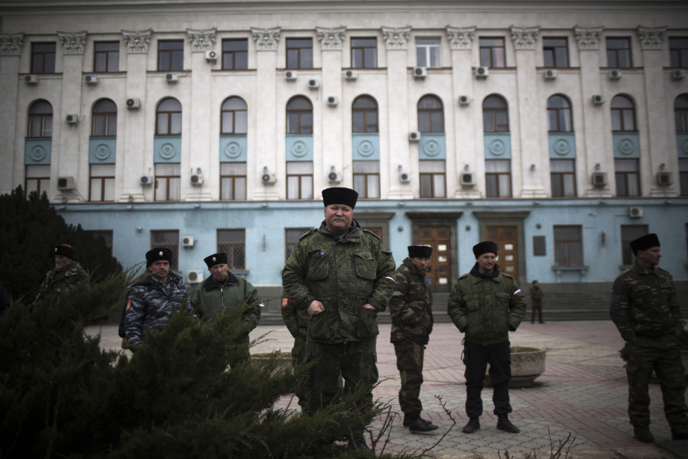 Cossacks and members of a voluntary self-defense force stand guard Saturday outside a government building in Lenin Square in Simferopol, Crimea, Ukraine.