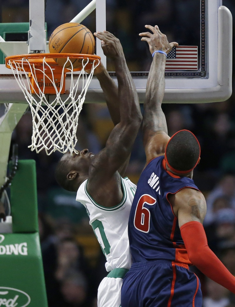Boston's Brandon Bass scores in front of Detroit's Josh Smith in the first quarter of the Celtics' 118-111 win over the Pistons in Boston on Sunday.