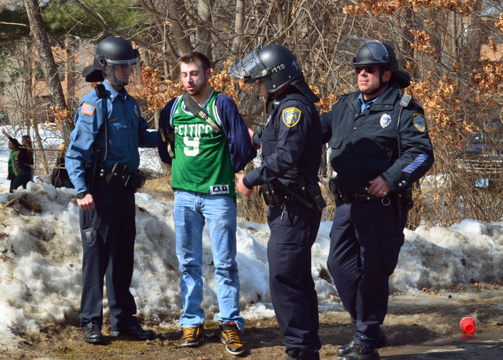 """Police detain a participant in the pre-St. Patrick's Day """"Blarney Blowout"""" near the University of Massachusetts in Amherst, Mass. on Saturday. Amherst police said early Sunday that 73 people had been arrested after authorities spent most of the day Saturday attempting to disperse several large gatherings around the campus for the party traditionally held the Saturday before spring break."""