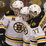 Bruins Reilly Smith, left, and Patrice Bergeron, right, celebrate with Torey Krug Sunday after Krug scored the go-ahead goal in the third period of Boston's 5-2 win over Florida.