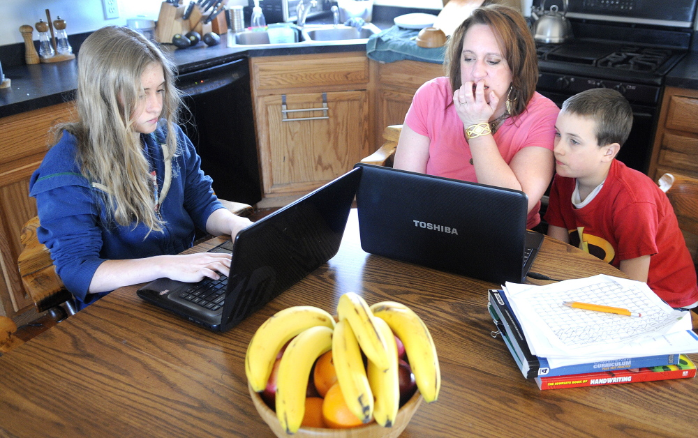 Kyrara Dawbin, 13, left, works on a lesson Thursday at the kitchen table with her mother, Karinna, and brother, Peter, 9, at their West Gardiner home. The Dawbins may enroll their children in Maine Connections Academy if it opens this fall.