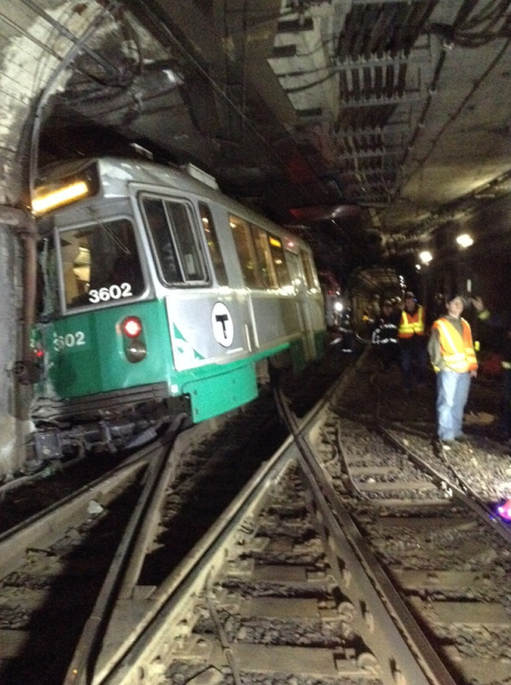 Fire and emergency personnel look over the scene of a MBTA Green Line train derailment in Boston on Monday. Boston Emergency Medical Services report at least seven people, including the derailed train's driver, complained of back pain. All passengers walked off the train unassisted.
